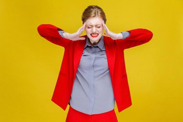 赤いスーツを着た生姜の赤い頭のビジネスウーマンは頭痛の片頭痛を持っています