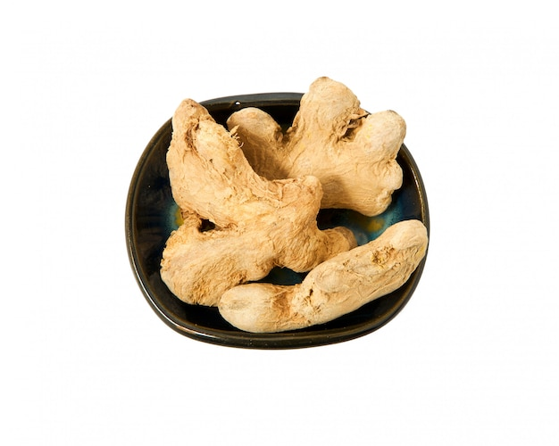 Ginger root in a bowl on a white background.