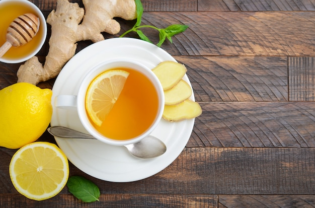 Ginger root tea with lemon and honey on wooden table, top view, copy space.