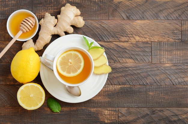 Ginger root tea with lemon and honey on wooden table. top view, flat lay, copy space.