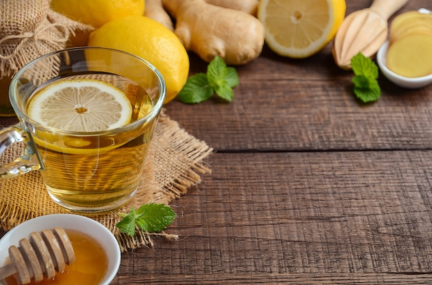 Ginger root tea with lemon and honey on wooden table.