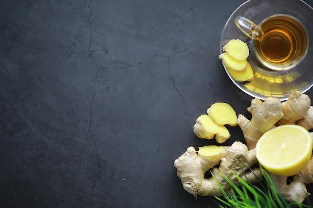 生姜の根全体とスライス。暗い背景にレモンとジンジャーティー。石の背景に新鮮なショウガの根。ビタミン。上面図。テキスト用の空き容量。