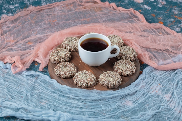 Ginger sesame cookies on a wooden platter.