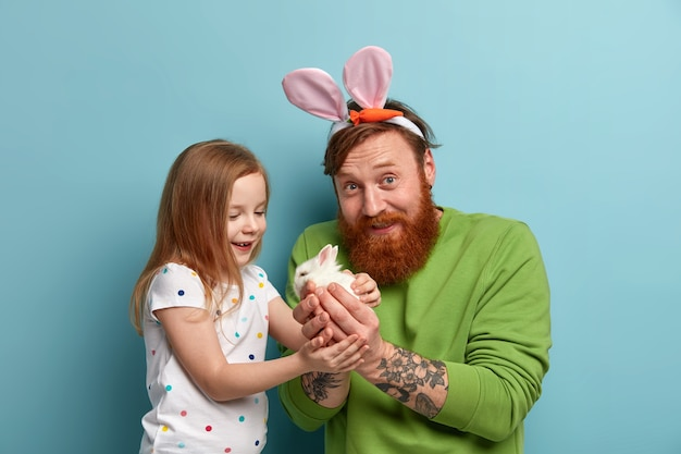 Ginger small adorable woman takes white little rabbit from fathers hands