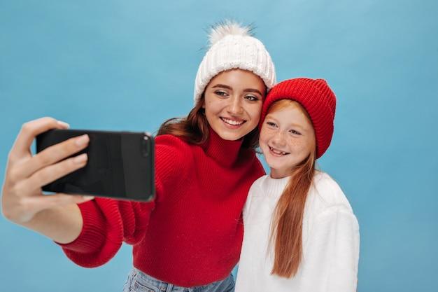 빨간 모자와 가벼운 와이드 스웨터를 입은 생강 어린 소녀가 포즈를 취하고 흰색 모자와 멋진 옷을 입은 매력적인 여동생과 사진을 찍습니다.