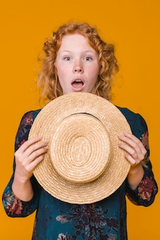 Ginger surprised young woman holding straw hat