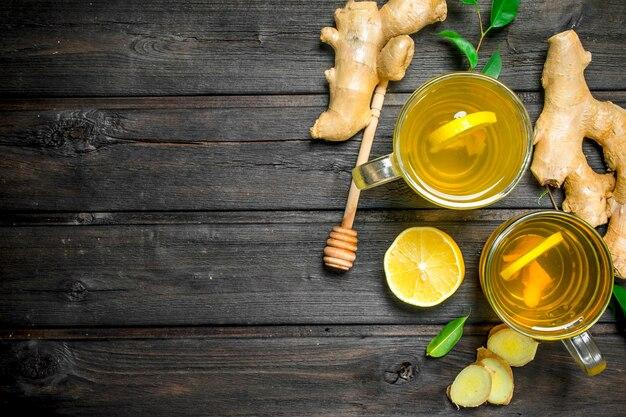 生姜茶とレモンと黒い木製のテーブルの葉