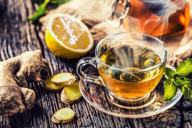 생강차 꿀 레몬과 민트 잎이 나무 테이블에 있습니다.