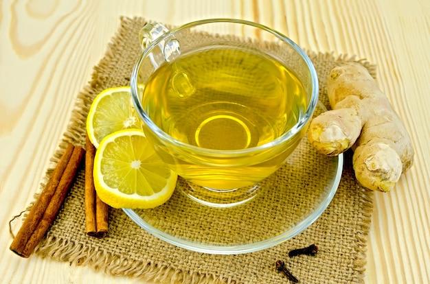 Имбирный чай в стеклянной чашке, две дольки лимона, корица, гвоздика, корень имбиря на салфетке из мешковины и деревянной доске