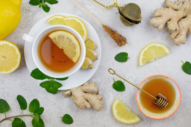 Ginger tea infusion in white cup with lemon slice, mint, honey, hot healthy beverage on white background.