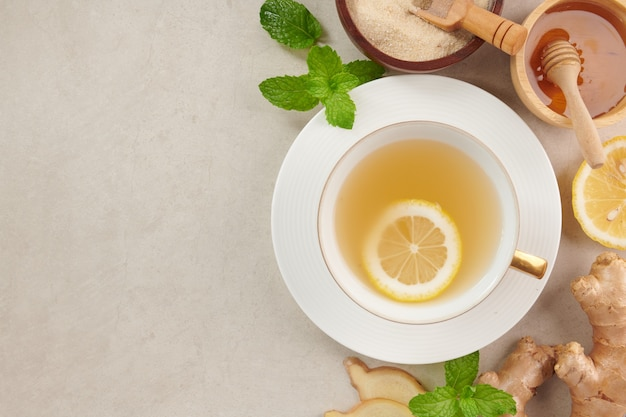 Ginger tea ingredients, healthy comforting and heating tea under simple recipe. ginger tea and ingredients - lemon, honey.top view. flat lay. freshly from home growth organic garden. food concept.