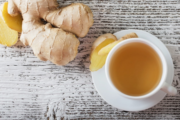 Ginger tea in a white cup on wooden background