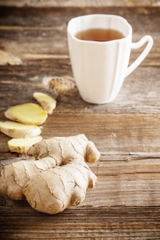 Ginger tea in a white cup on wooden table