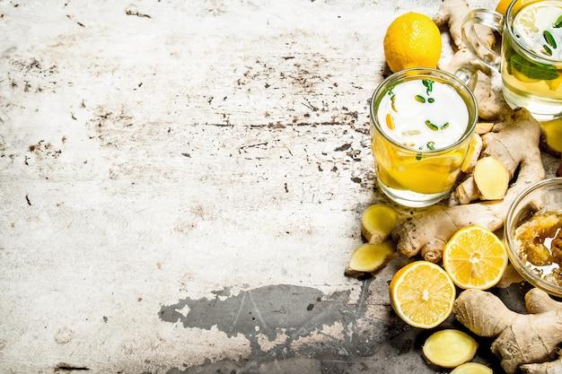 素朴なテーブルの上に蜂蜜とレモンとジンジャーティー。