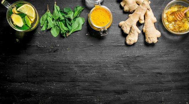 Ginger tea with ingredients on black chalkboard.