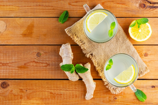 Ginger tea with lemon on a burlap napkin. two cups of ginger tea with mint on wooden background. top view