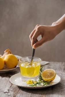 Ginger tea with lemon, ginger root and rosemary on wooden table. small glass transparent pitcher with hot drink.