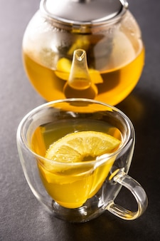 Ginger tea with lemon and honey in crystal glass on black table