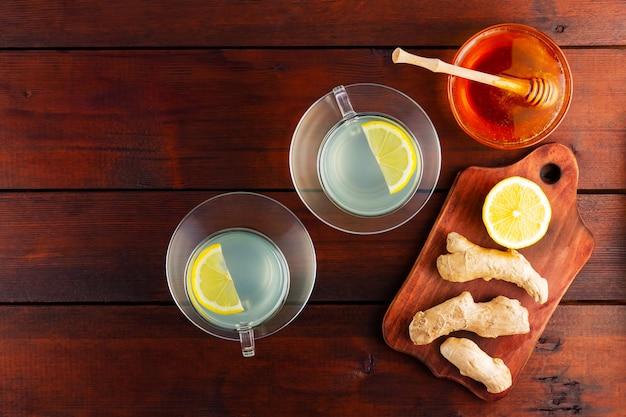 Имбирный чай с лимоном. две чашки имбирного чая с лимоном и медом на деревянных фоне. вид сверху