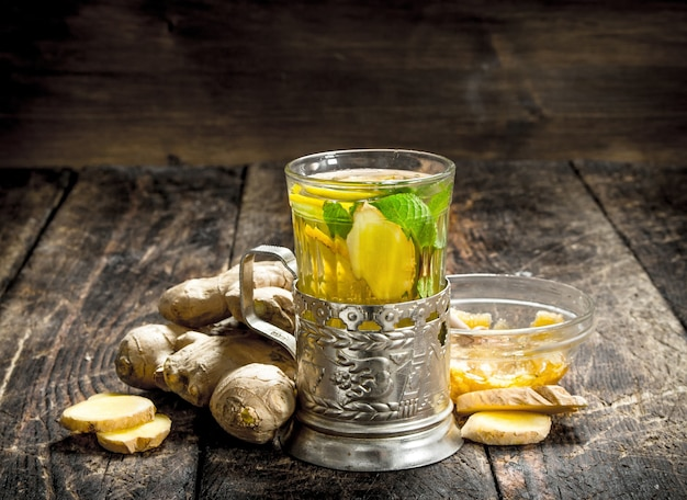 ミントとレモンのジンジャーティー。木製の背景に。
