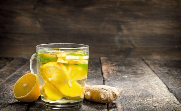Ginger tea with mint and lemon on wooden table.