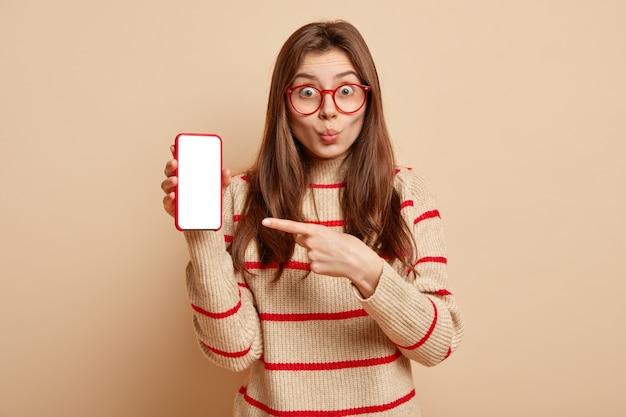 赤い眼鏡をかけている生姜ティーンエイジャー