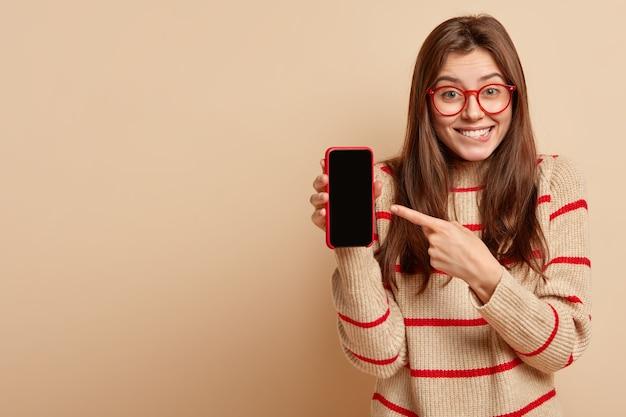 Adolescente dello zenzero che indossa occhiali rossi