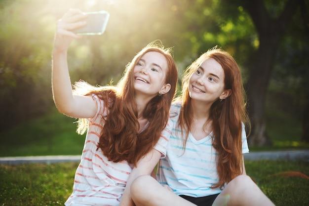 スマートフォンで自分撮りをしている生姜の双子の女の子が、喜んで笑っています。現代のテクノロジーはこれまで以上に人々をつなぎます。遠くの友達がいるのはとても楽しいです。