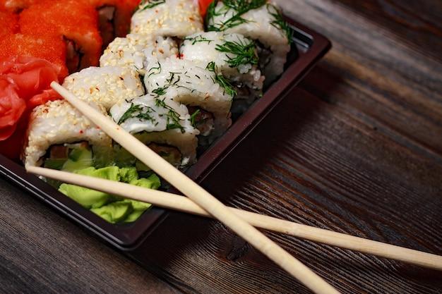 Роллы суши с имбирем васаби на деревянном столе деликатесные палочки азиатской кухни. фото высокого качества