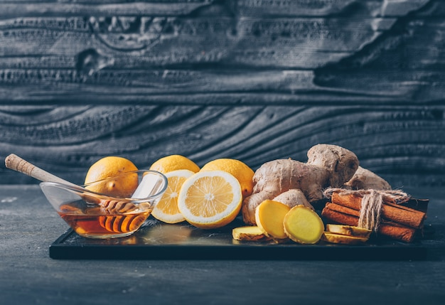 Ginger with lemon, honey and dry cinnamon pack top view on a dark textured background space for text