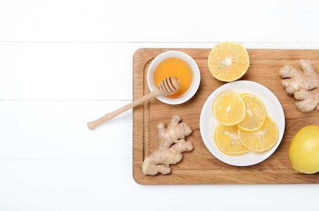 Имбирь с лимоном и травяным чаем на деревянном столе на белом фоне