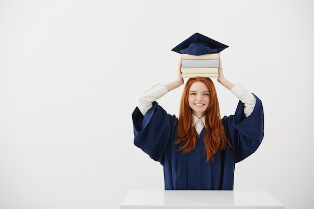 Ginger woman graduate smiling holding books on head under cap.