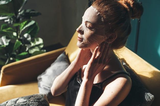 생강 여자는 홈 스파 절차 중에 얼굴 피부에 종이 마스크를 적용하고 있습니다