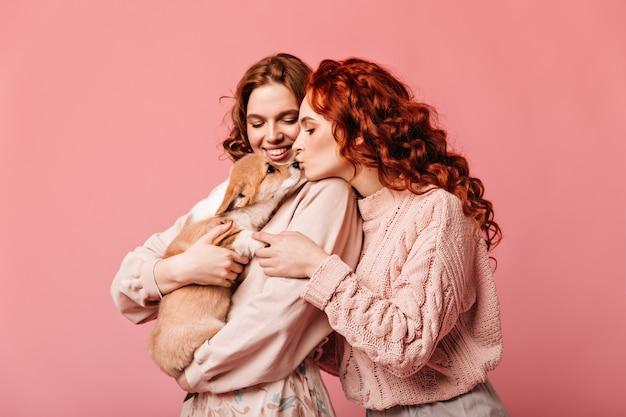 ピンクの背景の上の生姜の女性のキス犬。子犬とポーズをとる見事な女の子のスタジオショット。