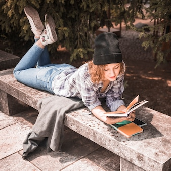 Ginger woman in plaid shirt reading book