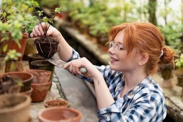温室で植物の世話をしている生姜の女性