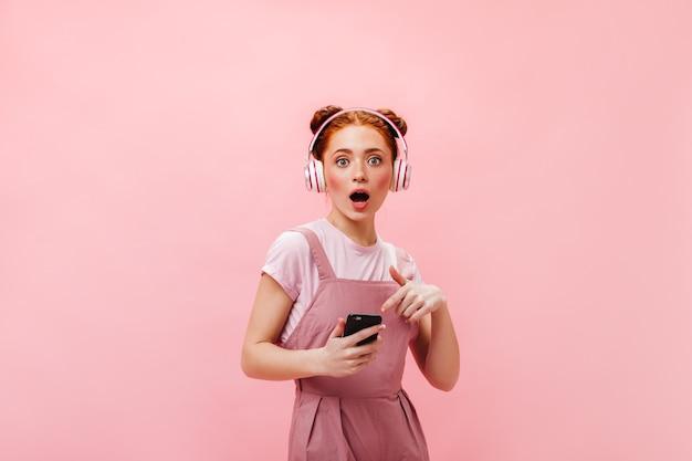 빵 귀여운 미소를 가진 생강 여자입니다. 노란색 눈 그림자를 가진 여자는 분홍색 배경에 벚꽃 인쇄 포즈와 흰색 탑을 입고.
