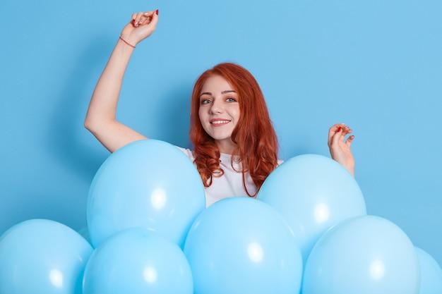 陽気な表情の生姜の女性は、手を上げ、音楽に合わせて踊り、誕生日パーティーで楽しんで、青い風船に囲まれ、誕生日の間に幸せな気分になり、女の子は休日を祝います。