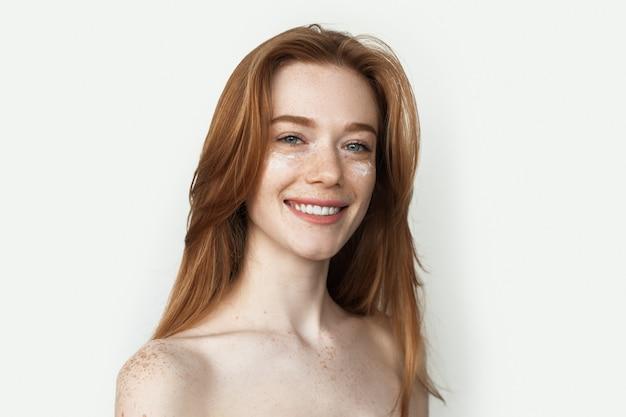Рыжая женщина с веснушками и кремом на лице улыбается с обнаженными плечами