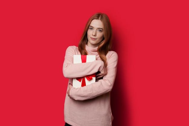 Рыжая женщина с веснушками обнимает подарок на красной стене студии, глядя в камеру в повседневной одежде