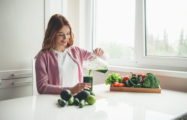Ginger woman with freckles is making fresh vegetable green juice at home putting it into a glass