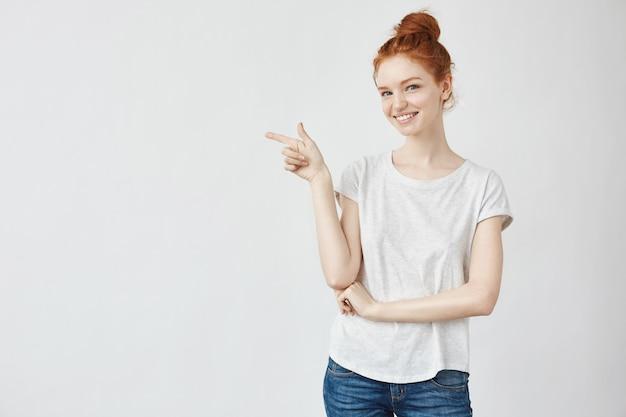 Donna dello zenzero con il dito indicante sorridente delle lentiggini nel lato.