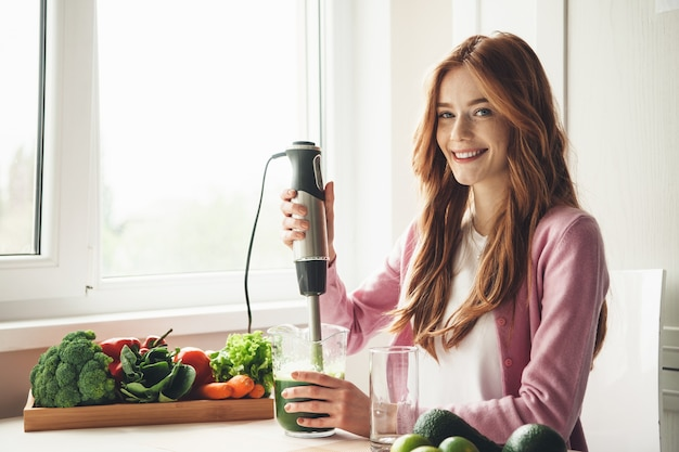 Ginger woman with freckles using an electrical squeezer and smile while making fresh vegetable juice