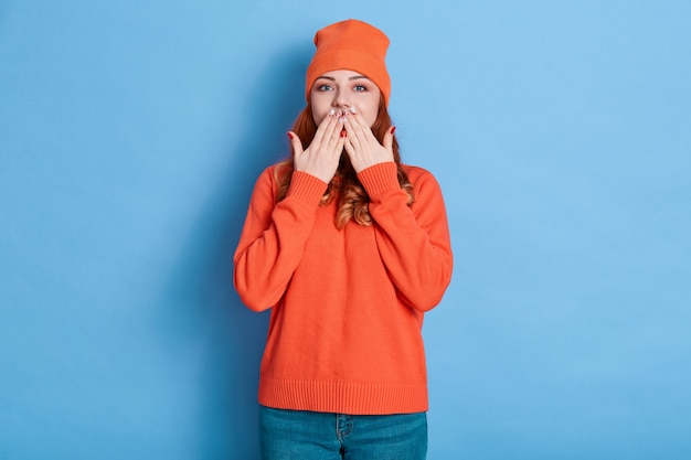 Ginger woman with positive emotions covering her mouth isolated on blue background, covering her mouth with palms