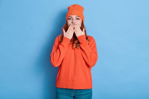 Рыжая женщина с положительными эмоциями прикрывает рот на синем фоне, прикрывая рот ладонями