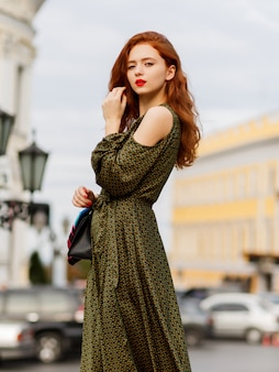 Ginger woman with red lips posing outdoor in warm spring day.