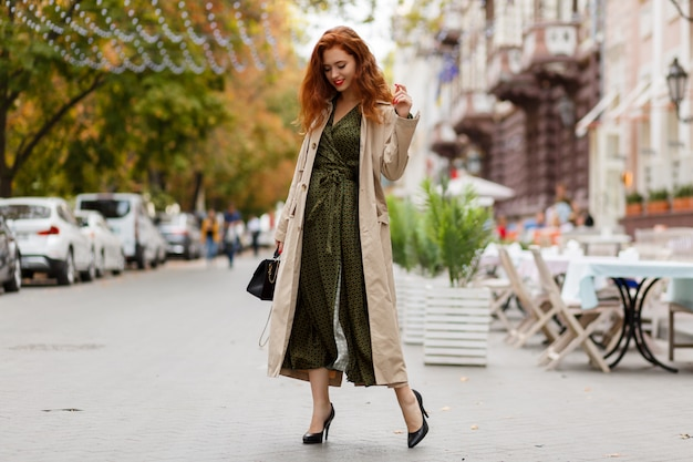 Ginger woman with wavy hairs in beige coat. red lips and nail.
