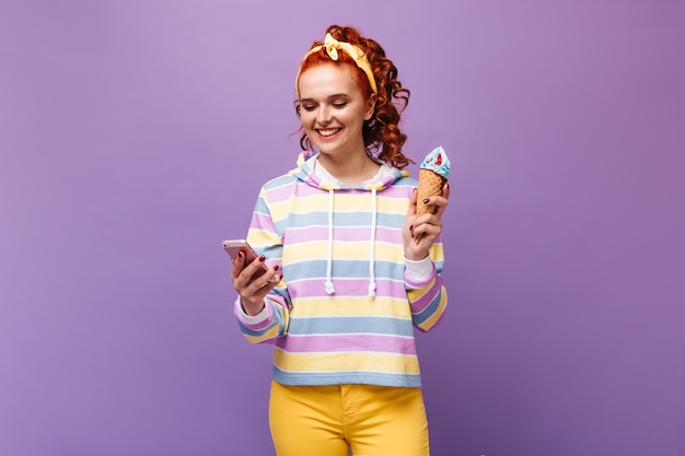 Ginger woman in yellow hair dressing with smile is chatting in smartphone and holding blue ice cream