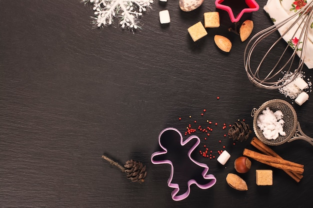 Ginger xmas cookies baking concept over black stone background