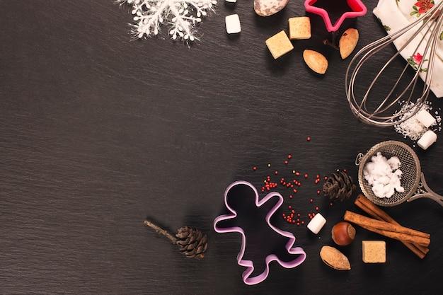 검은 돌 배경 위에 생강 크리스마스 쿠키 베이킹 개념